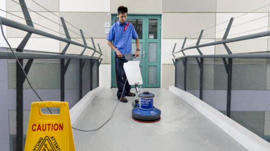 Sodexo employee cleaning a walkway with a buffing machine