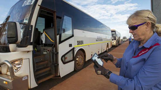 Sodexo employee inputting information in to a tablet whilst standing in front of a coach